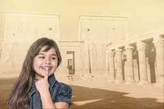 Smiling little girl is standing in front of Philae temple. Royalty Free Stock Photos