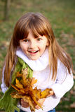 Smiling little girl standing and holding leaves Royalty Free Stock Image