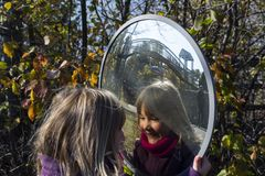 Little girl staring at her reflection in mirror. Smiling little girl staring at her reflection in a round traffic mirror with fall foliage in the background Royalty Free Stock Photo