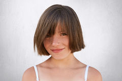 Smiling little girl with stylish hairdo, dark eyes and freckled face posing against white background. Pretty girl with happy expre. Ssion looking at camera with royalty free stock images
