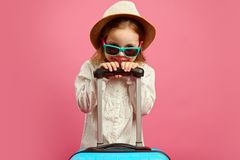 Smiling little girl in sunglasses and straw hat, holding suitcase on isolated pink, sincerely expresses joy and royalty free stock photo