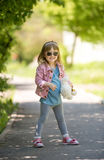 Smiling little girl with sunglasses in park. Smiling little girl with sunglasses walking in spring park Stock Images