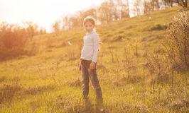 Smiling little girl on sunlight in countryside. Smiling little girl standing on sunlight in countryside on a hill Royalty Free Stock Photos