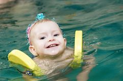 Smiling little girl swimming at Royalty Free Stock Image