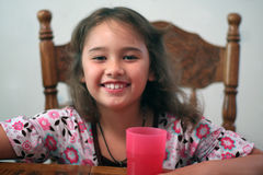 Smiling little girl at table. A smiling little girl (age 6) sits at the kitchen table with a glass of water. She has a huge smile and brown hair and eyes and is Royalty Free Stock Images