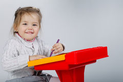 Smiling little girl at the table draw Stock Photo
