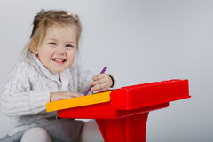 Smiling little girl at the table draw Stock Image