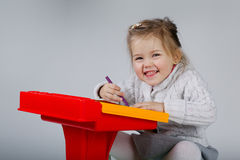 Smiling little girl at the table draw Royalty Free Stock Image
