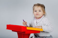 Smiling little girl at the table draw Stock Images