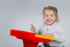 Smiling little girl at the table draw Royalty Free Stock Photography
