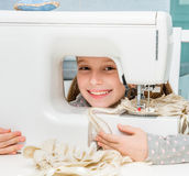 Smiling little girl at the table with sewing Royalty Free Stock Image