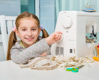 Smiling little girl at the table with sewing Royalty Free Stock Photos