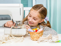 Smiling little girl at the table with sewing