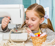 Smiling little girl at the table with sewing Stock Photo