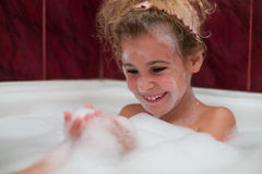 Smiling little girl taking a bath with foam stock image