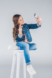 Smiling little girl taking selfie with smartphone and gesturing. Adorable smiling little girl taking selfie with smartphone and gesturing Royalty Free Stock Image