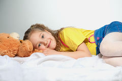 A smiling little girl with a teddy bear is lying on a white clot. H. She is wearing blue jean skirt and yellow t-shirt. Studio photo Stock Images