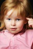 Smiling little girl thinking. On dark background Royalty Free Stock Photos