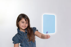 Smiling little girl is touching transparent rectangle by her ind. On the left side standing smiling little girl is touching a blank transparent rectangle  by her Stock Images