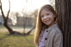 Smiling Little Girl Beside A Tree Royalty Free Stock Photography