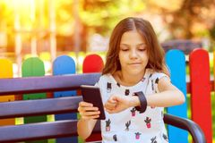Happy kid with trendy gadgets synchronizing smartwatch with smartphone while sitting on bench in park. Smiling little girl using modern wearable smart watch and royalty free stock photo