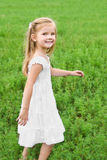 Smiling little girl is walking on the green field Royalty Free Stock Image