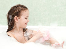 Smiling little girl washing in bath Stock Photos