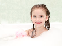 Smiling little girl washing in bath Stock Images