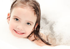 Smiling little girl washing in bath with foam Stock Photography