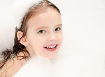 Smiling little girl washing in bath with foam Royalty Free Stock Photo