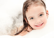 Smiling little girl washing in bath with foam Stock Image