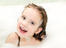 Smiling little girl washing in bath with foam Royalty Free Stock Photography