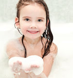 Smiling little girl washing in bath with foam Stock Photo