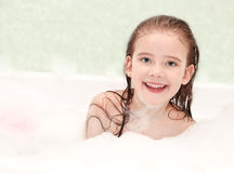 Smiling little girl washing in bath Stock Photography