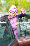 Smiling little girl waving red car Stock Images