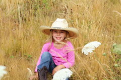 Smiling little girl wearing large hat. A smiling little 6 year old girl with blond hair wearing a big brimmed cowboy hat sitting in tall grass and white wild Royalty Free Stock Photography