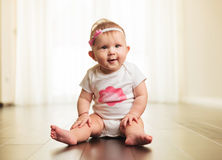 Smiling little girl wearing pink headband sitting stock photo