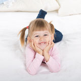 Smiling little girl in white bed Stock Photo