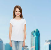 Smiling little girl in white blank t-shirt. Advertising, childhood, city and people concept - smiling little girl in white blank t-shirt over business center Stock Photos