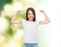 Smiling little girl in white blank t-shirt. Advertising, childhood, gesture, ecology and people - smiling little girl in white blank t-shirt with raised arms Stock Photos