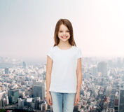 Smiling little girl in white blank t-shirt. Advertising, childhood and people concept - smiling little girl in white blank t-shirt over city background Stock Images