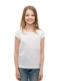 Smiling little girl in white blank t-shirt. Advertising and t-shirt design concept - smiling little girl in white blank t-shirt over white background Royalty Free Stock Image