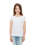 Smiling little girl in white blank t-shirt. Advertising and t-shirt design concept - smiling little girl in white blank t-shirt over white background Stock Images
