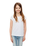 Smiling little girl in white blank t-shirt. Advertising and t-shirt design concept - smiling little girl in white blank t-shirt over white background Stock Image