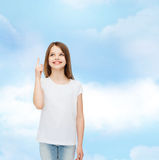 Smiling little girl in white blank t-shirt. Advertising, dream, childhood, gesture and people - smiling little girl in white blank t-shirt pointing finger up Stock Images
