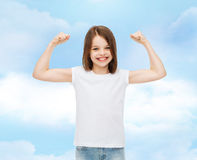 Smiling little girl in white blank t-shirt. Advertising, dream, childhood, gesture and people - smiling little girl in white blank t-shirt with raised arms over Stock Photo