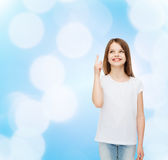 Smiling little girl in white blank t-shirt. Advertising, gesture, childhood and people - smiling little girl in white blank t-shirt pointing finger up over blue Stock Photography