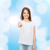 Smiling little girl in white blank t-shirt. Advertising, gesture, childhood and people - smiling little girl in white blank t-shirt pointing finger at you over Stock Photography
