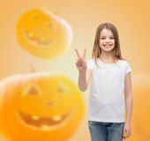 Smiling little girl in white blank t-shirt. Advertising, holidays, gesture and people concept - smiling little girl in white blank t-shirt showing victory sign Royalty Free Stock Photography