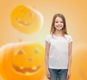Smiling little girl in white blank t-shirt. Advertising, holidays and people concept - smiling little girl in white blank t-shirt over halloween pumpkins Stock Images